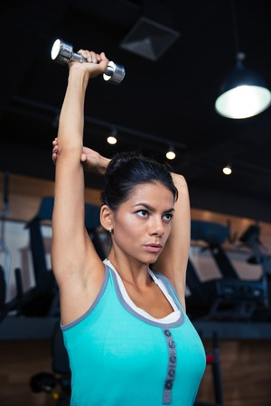 workout: Attractive young woman workout with dumbbell in gym Stock Photo