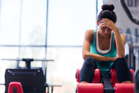 tired woman: Tired sports woman sitting on exercises machine in fitness gym