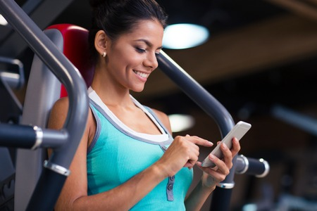 mobile telephone: Portrait of a cheerful sports woman using smartphone in fitness gym