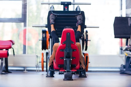laying abs exercise: Portrait of a sports woman workout on exercises machine at fitness gym