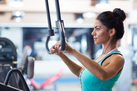 Sports woman workout on exercises machine in fitness gym Stock Photo