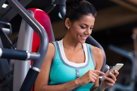 Portrait of a happy fitness woman using smartphone in gym