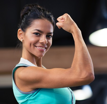boast: Smiling beautiful woman showing her biceps in gym