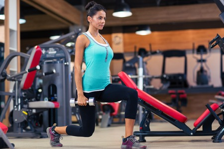 workout: Full length portrait of a young woman workout with dumbbells in fitness gym