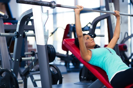 woman lying: Beautiful woman doing exercises with barbell on the bench in fitness gym
