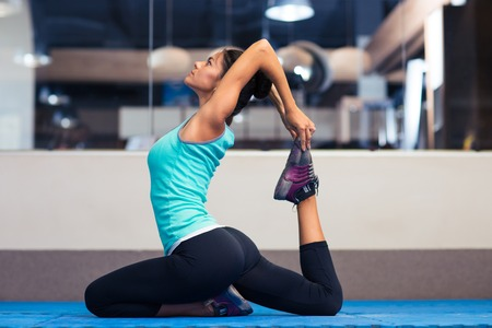 gorgeous woman: Portrait of a young woman stretching in gym