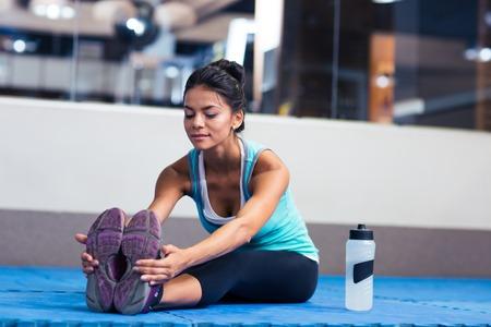 estiramientos: Retrato de una mujer de estiramiento en el gimnasio de deportes