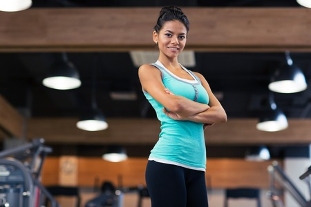 Portrait of a happy sports woman standing with arms folded in fitness gym 版權商用圖片