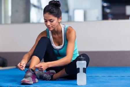 mujer con corbata: Mujer Deportes atar cordones de los zapatos en el gimnasio
