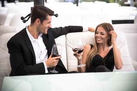 Happy elegant couple drinking red wine in restaurant Standard-Bild