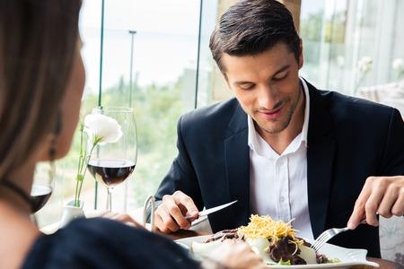 pareja comiendo: Feliz pareja comiendo en un restaurante con un vino tinto Foto de archivo