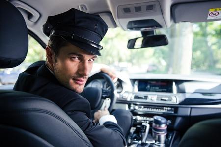 Portret van een knappe mannelijke chauffeur in een auto zit Stockfoto