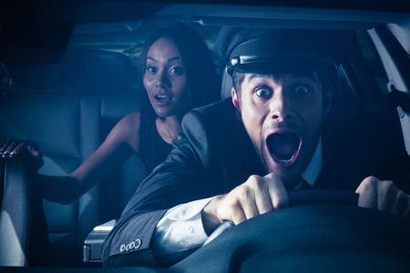 Male chauffeur with woman on back seat gets into car crash and makes ridiculous face Stock Photo