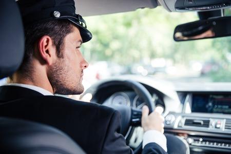 Portrait of a handsome male chauffeur riding car