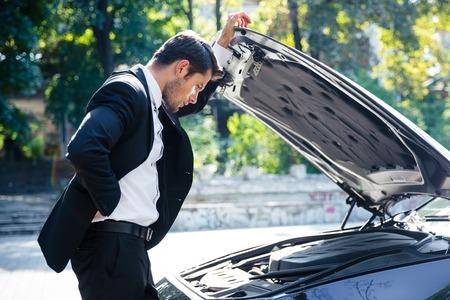inconvenience: Man standing near broken car with open hood