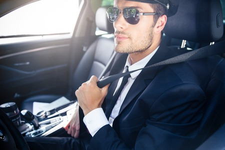 Portrait of a handsome male chauffeur in sunglasses sitting in a car Stock Photo