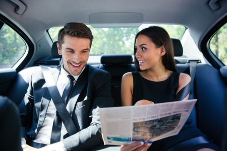 Happy couple reading newspaper in car Stock Photo