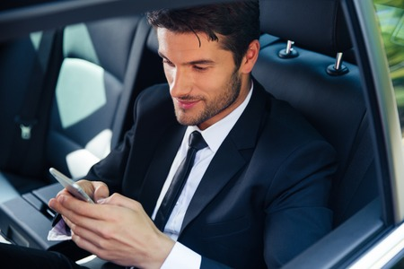 Handsome businessman using smartphone in car