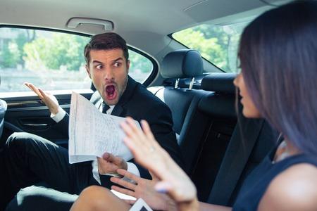 personas enojadas: Angry hombre en posesión de documentos que grita en un mujer en coche