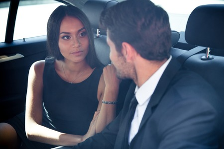 back seat: Businessman and businesswoman talking in back seat of car
