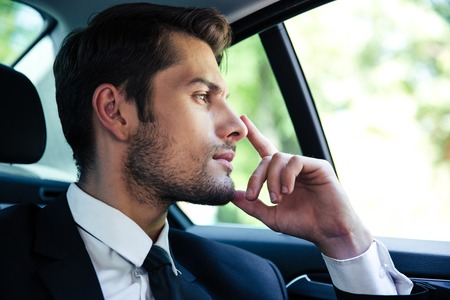 expensive: Thoughtful businessman riding in car