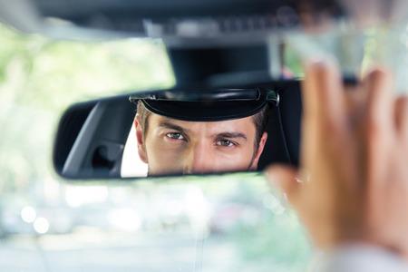 Mannelijke chauffeur in een auto zit en kijken naar zijn spiegelbeeld in een spiegel