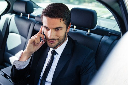 Happy businessman talking on the phone in car