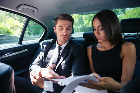 concerning: Business couple reading documents in car