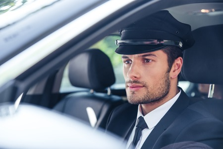 Portrait of a handsome male chauffeur sitting in a car