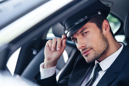 Portrait of a handsome male chauffeur sitting in a car and making saluting gesture Archivio Fotografico