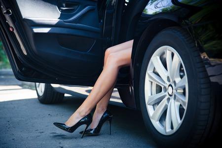 piernas con tacones: Retrato del primer de una piernas femeninas en coche