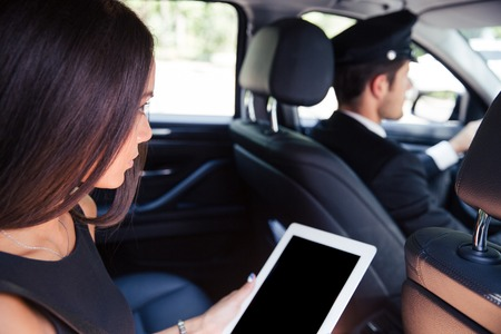 cab: Woman using tablet computer while riding in taxi Stock Photo