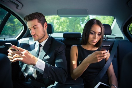 Businessman and businesswoman using smartphone on back seat in car Foto de archivo