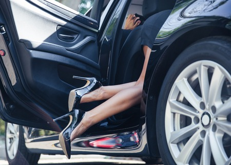 Closeup portrait of a female legs in car