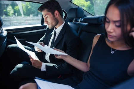 back seat: Businesswoman and businessman reading papers on back seat in car Stock Photo