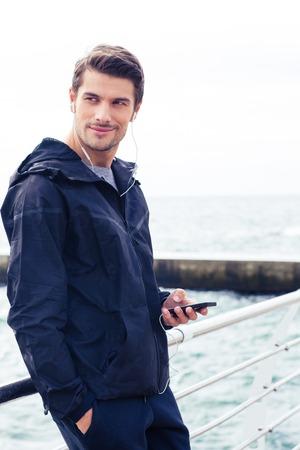 Portret van een knappe man met behulp van smartphone met een koptelefoon buiten