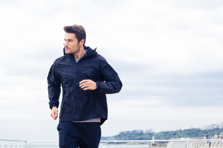 handsome young athletic: Sports man running at the morning outdoors