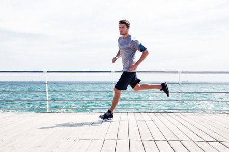 Full length portrait of a sports man running outdoors near sea