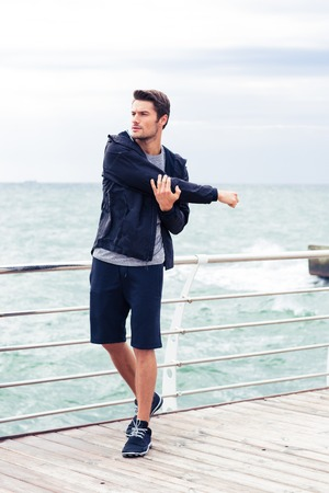 stretching: Portrait of a handsome sports man stretching hands outdoors in the morning with sea on background