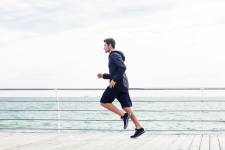 hacer footing: Vista lateral retrato de un hombre de los deportes se ejecuta cerca del mar Foto de archivo