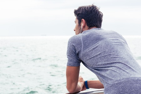 cool guy: Back view portrait of a sports man looking at sea outdoors