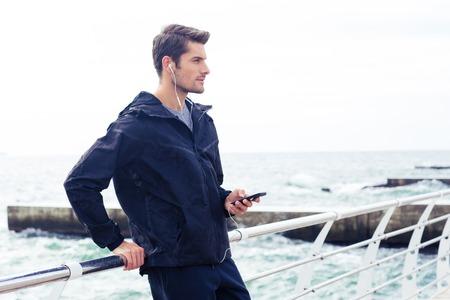 hombres guapos: Retrato de un hombre guapo escuchar m�sica en el tel�fono inteligente al aire libre