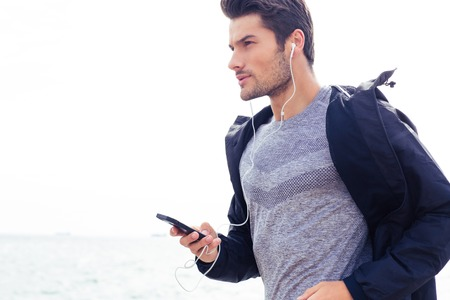 Portrait of a young sports man running with headphones Stock Photo