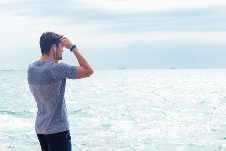 sports wear: Portrait of a man in sports wear looking at the sea outdoors Stock Photo