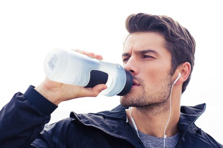 bodies of water: Portrait of a handsome man in headphones drinking water isolated on a white background