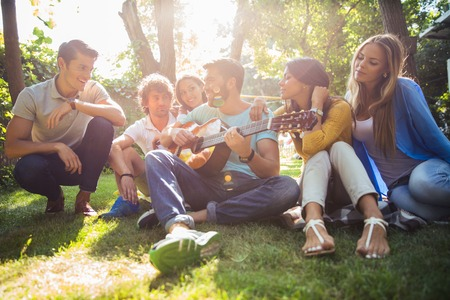 Group of happy friends with guitar having fun outdoor Stock Photo