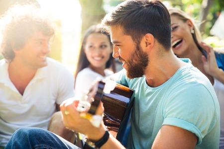 cantando: Grupo de amigos felices con la guitarra divierten al aire libre Foto de archivo