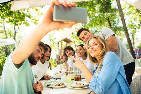 making fun: Portrait of a cheerful friends making selfie photo on smartphone in outdoor restaurant Stock Photo