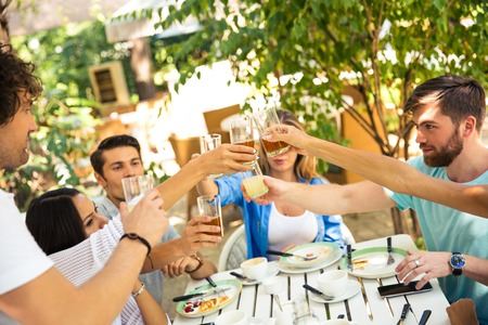 proposing a toast: Group of a friends making toast around table at dinner party in outdoor restaurant