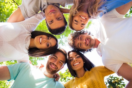 Group of friends hugging together at the park in a circle Stock Photo